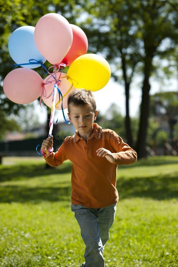 Weinig jongen die met ballons loopt stock fotografie