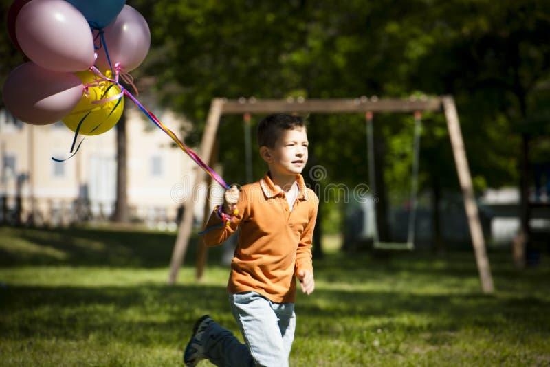Weinig jongen die met ballons loopt stock foto's