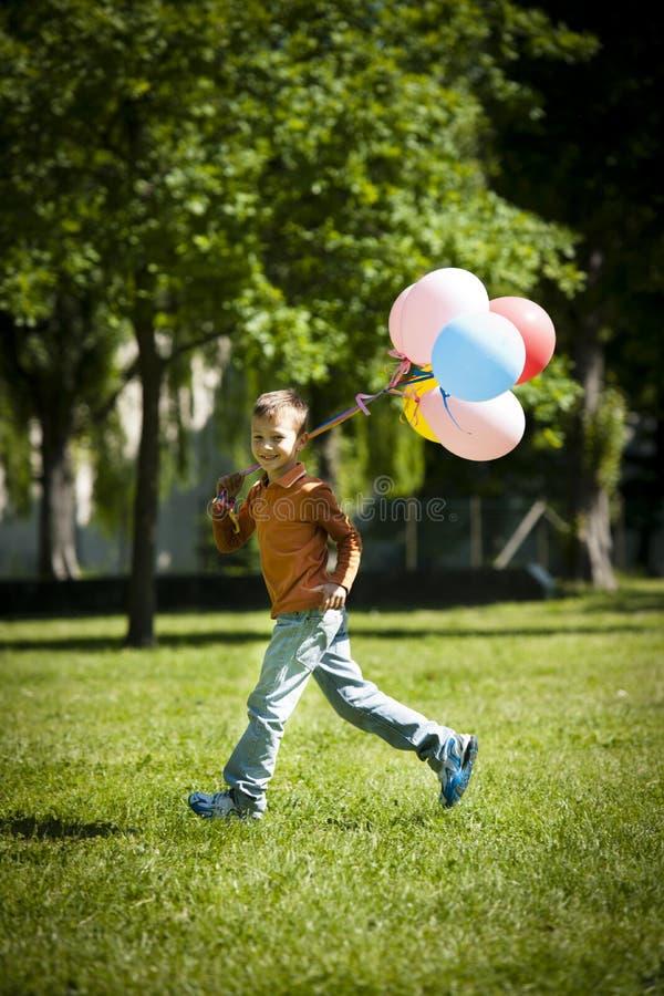 Weinig jongen die met ballons loopt stock afbeeldingen
