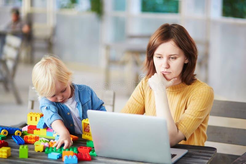 Weinig jongen die met bouw spelen blokkeert terwijl zijn moeder die aan computer werken royalty-vrije stock afbeelding