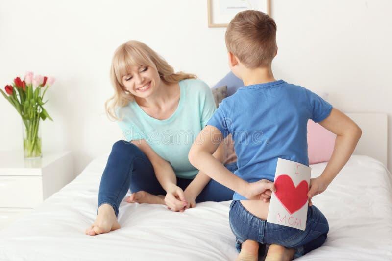 Weinig jongen die met de hand gemaakte kaart voor moeder achter zijn rug in slaapkamer verbergen royalty-vrije stock foto's