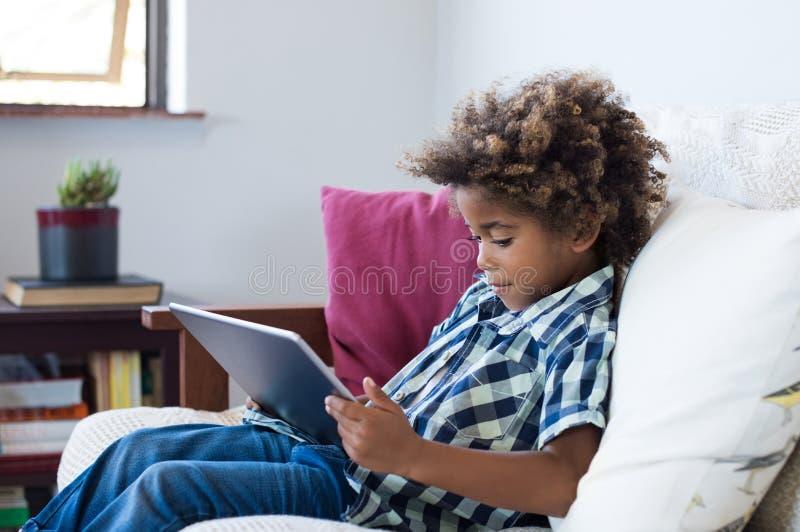 Weinig jongen die met digitale tablet spelen stock afbeelding