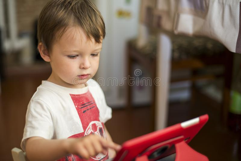 Weinig jongen die met digitale tablet spelen jong geitje gebruikend een digitale tablet royalty-vrije stock foto's