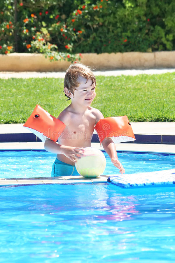 Weinig jongen die met een bal in een zwembad speelt royalty-vrije stock afbeelding
