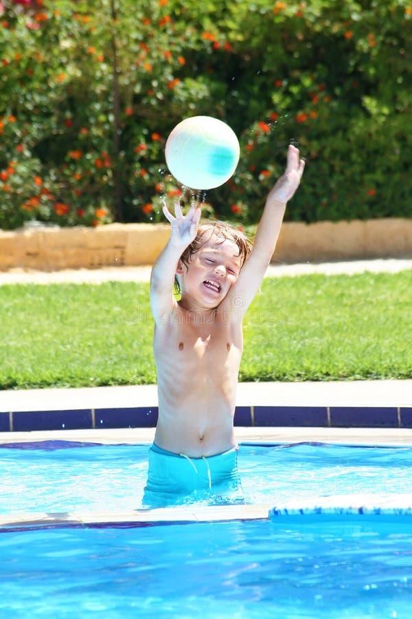 Weinig jongen die met een bal in een zwembad speelt royalty-vrije stock foto