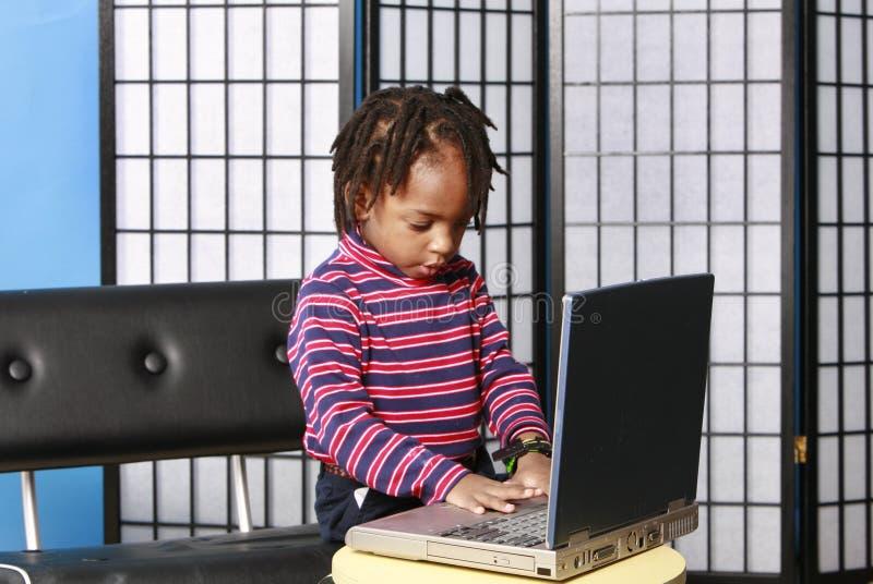 Weinig jongen die met een computer speelt royalty-vrije stock foto