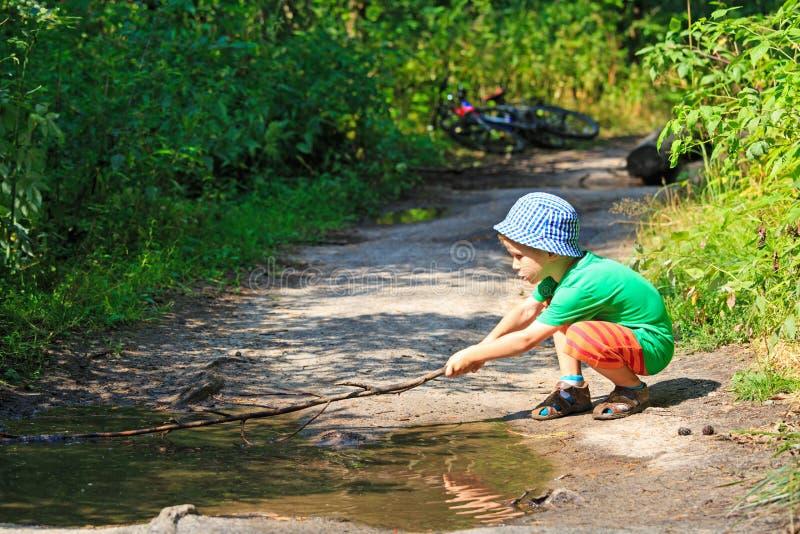 Weinig jongen die met een stok in watervulklei spelen stock afbeelding