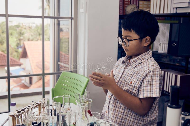 Weinig jongen die met glazen beker houden royalty-vrije stock afbeelding