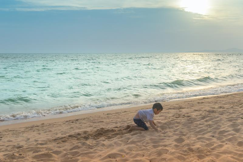Weinig jongen die met golf en zand in Pattaya-Strand Thailand spelen royalty-vrije stock fotografie