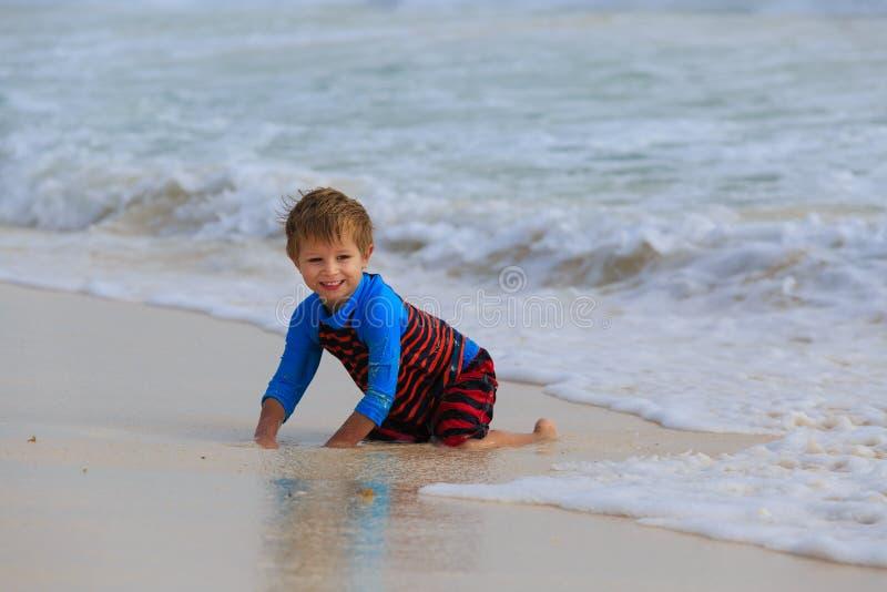 Weinig jongen die met golven op zandstrand spelen royalty-vrije stock afbeelding