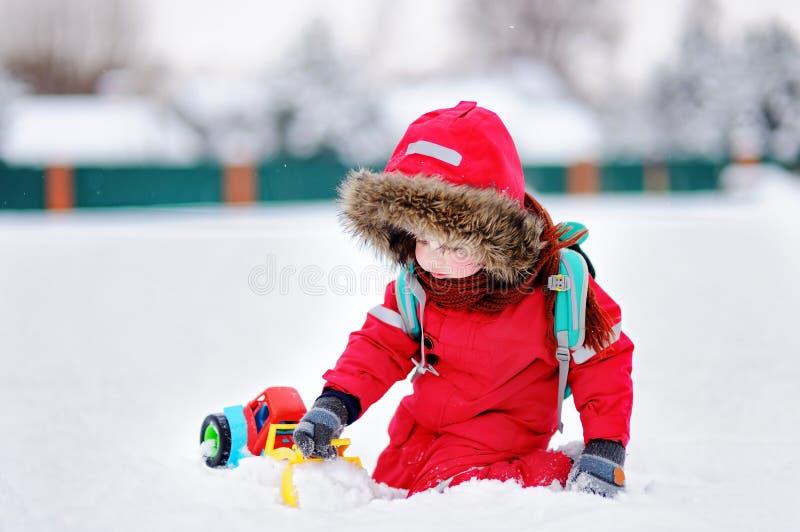 Weinig jongen die met helder autostuk speelgoed en verse sneeuw spelen royalty-vrije stock afbeeldingen