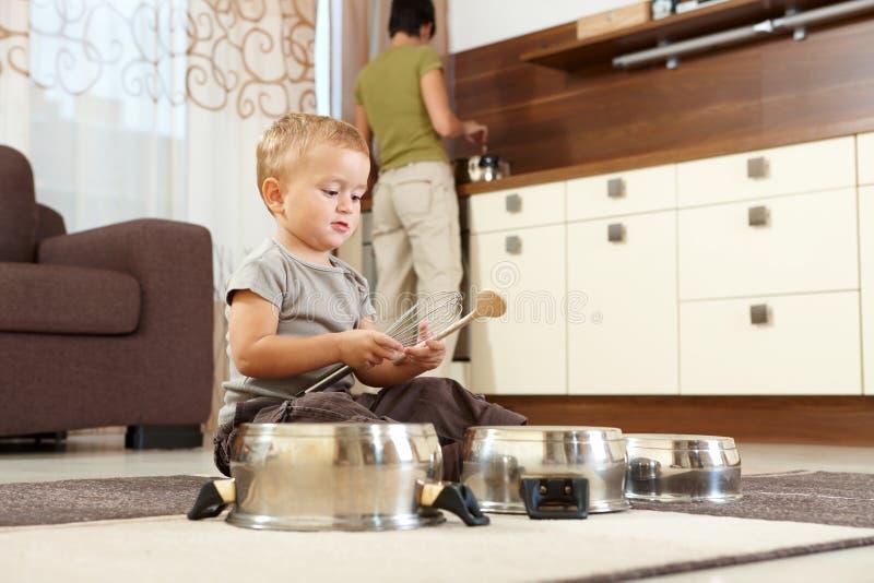 Weinig jongen die met het koken van potten speelt stock foto