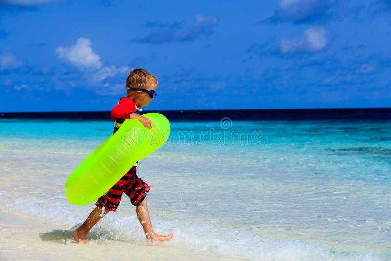 Weinig jongen die met het levensring bij tropisch spelen royalty-vrije stock fotografie