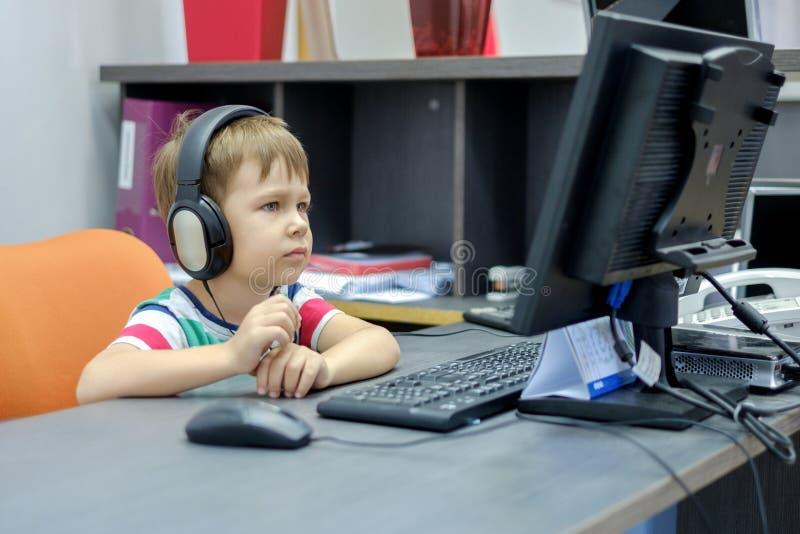 Weinig jongen die met hoofdtelefoons bij computer in bureau zitten stock foto's