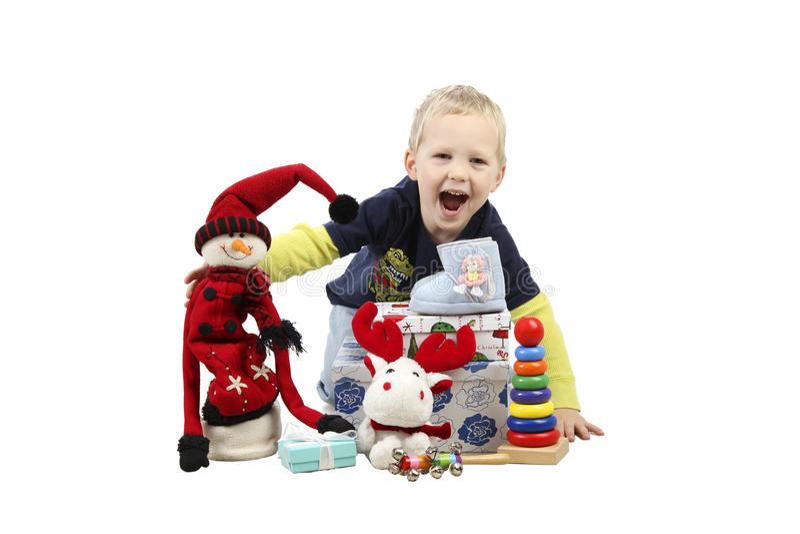 Weinig jongen die met Kerstmisgiften en speelgoed spelen die over witte achtergrond worden geïsoleerd stock foto's