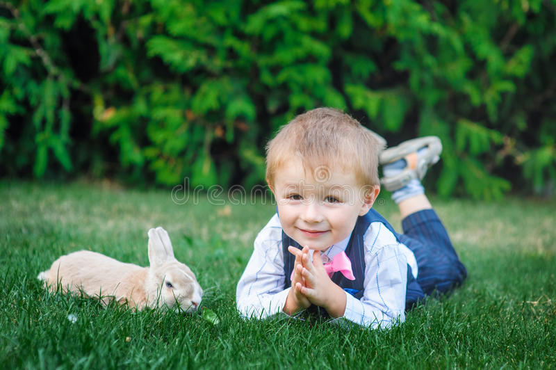 Weinig jongen die met konijn op groen gras spelen stock afbeelding