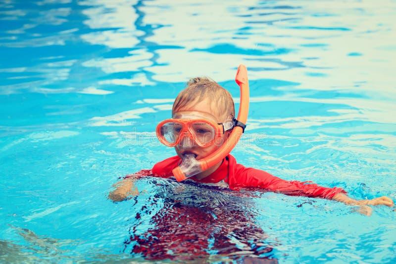 Weinig jongen die met masker in de pool zwemmen royalty-vrije stock foto