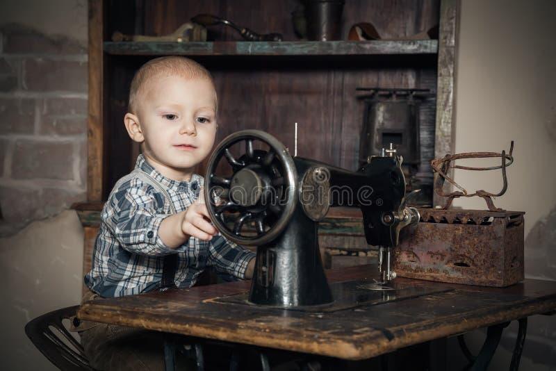 Weinig jongen die met naaien-machine speelt royalty-vrije stock afbeeldingen