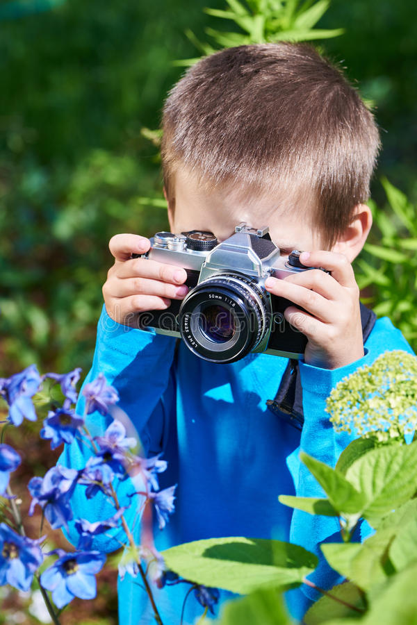 Weinig jongen die met retro SLR-camera macrobloemen schieten stock fotografie
