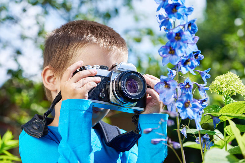 Weinig jongen die met retro SLR-camera macrobloemen schieten royalty-vrije stock foto's