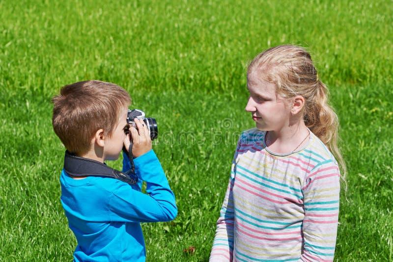 Weinig jongen die met retro SLR-camera meisje schieten stock afbeelding