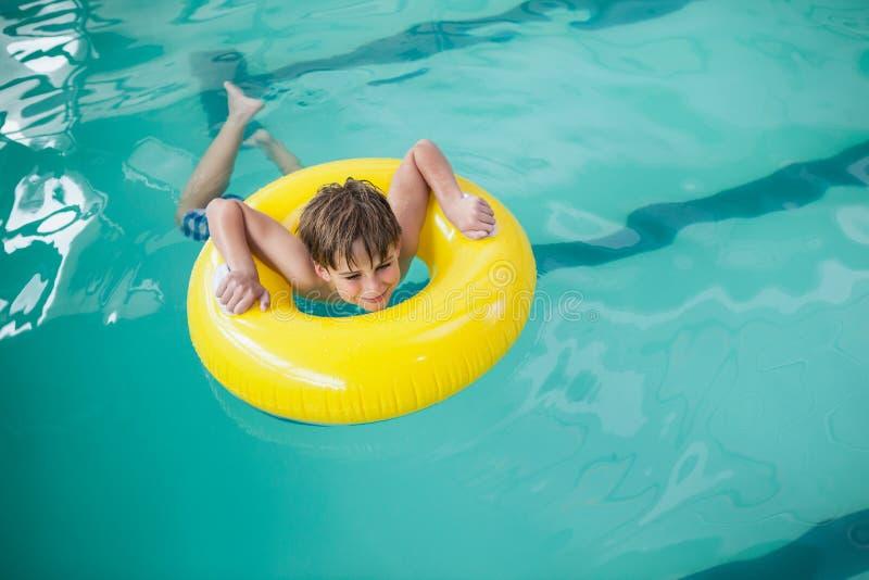 Weinig jongen die met rubberring zwemmen stock fotografie