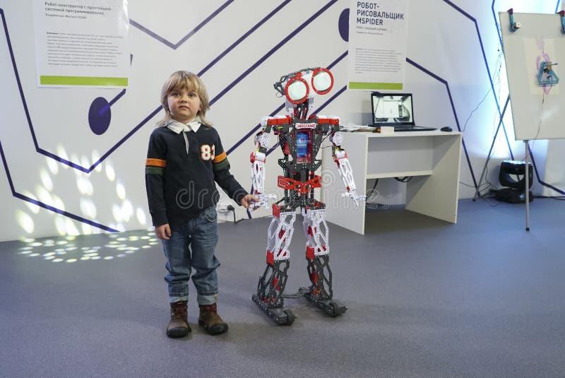 Weinig jongen die met slimme robot interactie aangaan stock foto