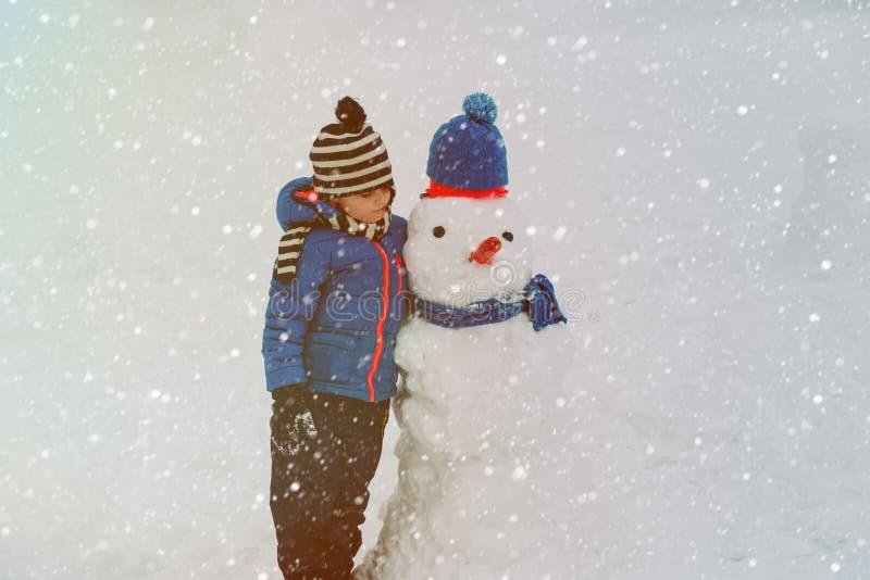 Weinig jongen die met sneeuwman in aard spelen royalty-vrije stock foto