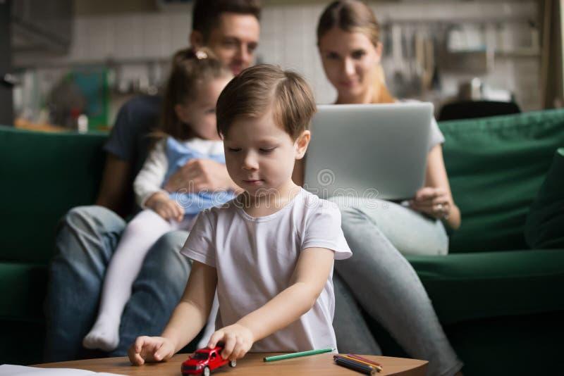 Weinig jongen die met stuk speelgoed auto's spelen terwijl ouders die samen zitten stock fotografie
