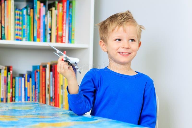 Weinig jongen die met stuk speelgoed vliegtuig spelen die over vliegen stock foto's