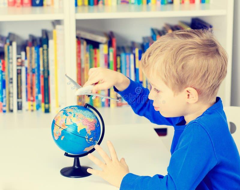 Weinig jongen die met stuk speelgoed vliegtuig spelen die rond vliegen royalty-vrije stock afbeelding