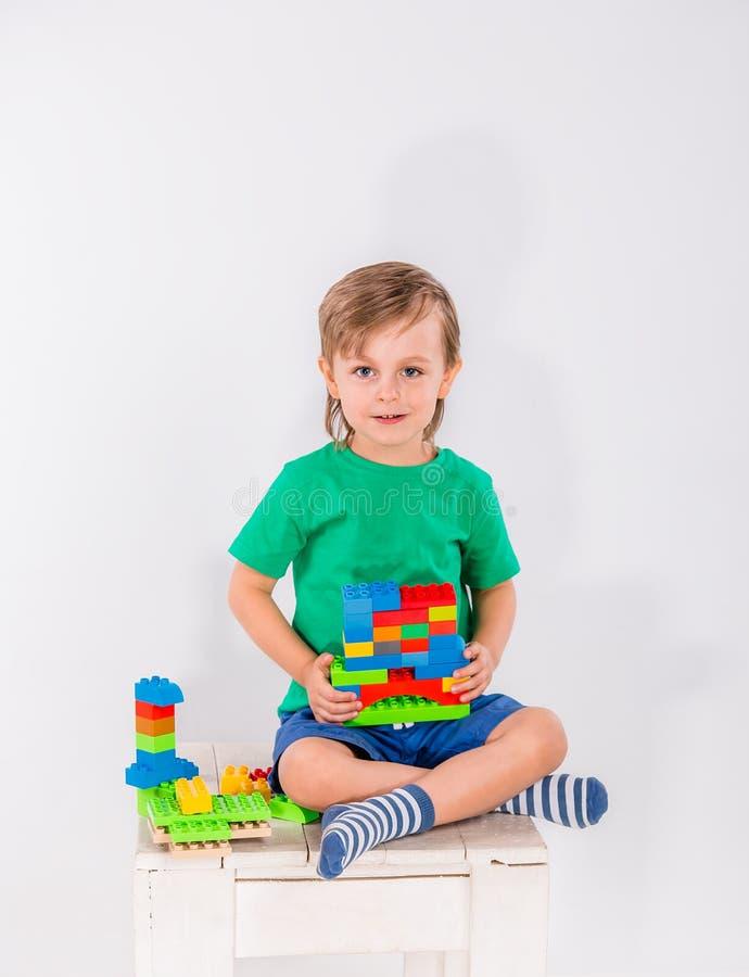 Weinig jongen die met veel kleurrijk plastiek spelen blokkeert aannemer royalty-vrije stock fotografie