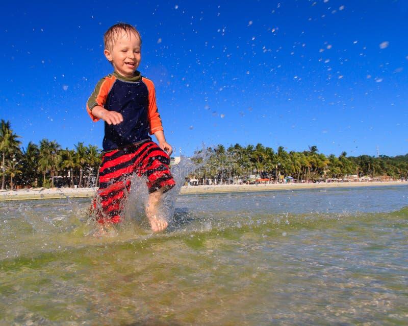 Weinig jongen die met water op het strand spelen royalty-vrije stock afbeelding