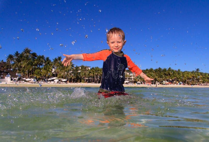 Weinig jongen die met water op het strand spelen royalty-vrije stock foto's