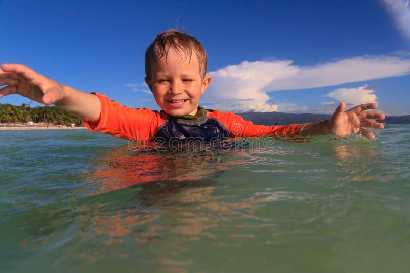 Weinig jongen die met water op het strand spelen stock foto's
