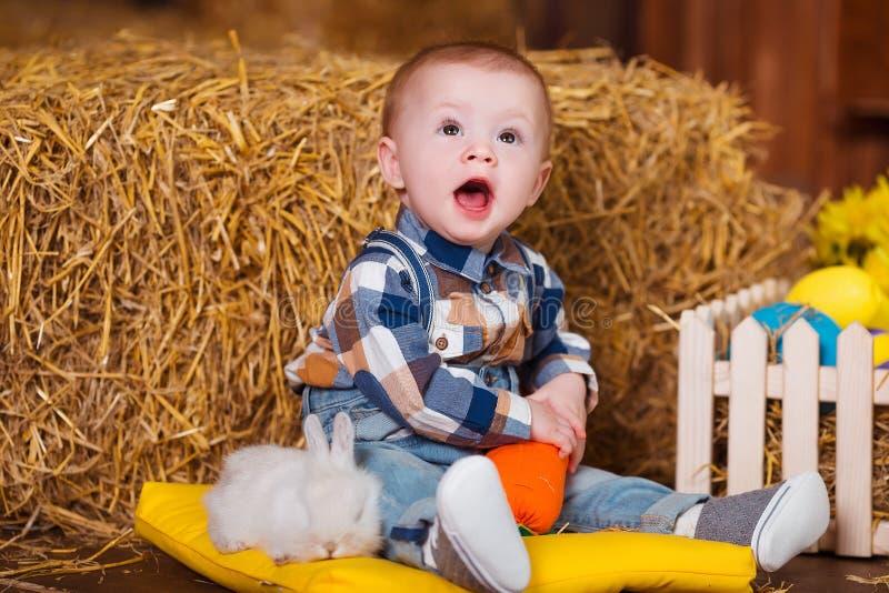 Weinig jongen die met wit konijn spelen binnen De pret van de lentepasen voor kinderen Gelukkig kinderjarenconcept stock afbeelding