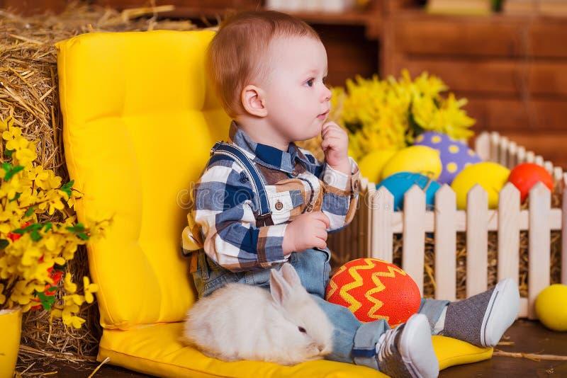 Weinig jongen die met wit konijn spelen binnen De pret van de lentepasen voor kinderen Gelukkig kinderjarenconcept royalty-vrije stock afbeelding