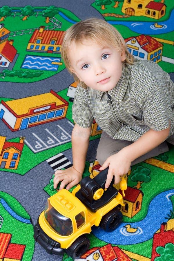 Weinig jongen die met zijn stuk speelgoed speelt. royalty-vrije stock fotografie