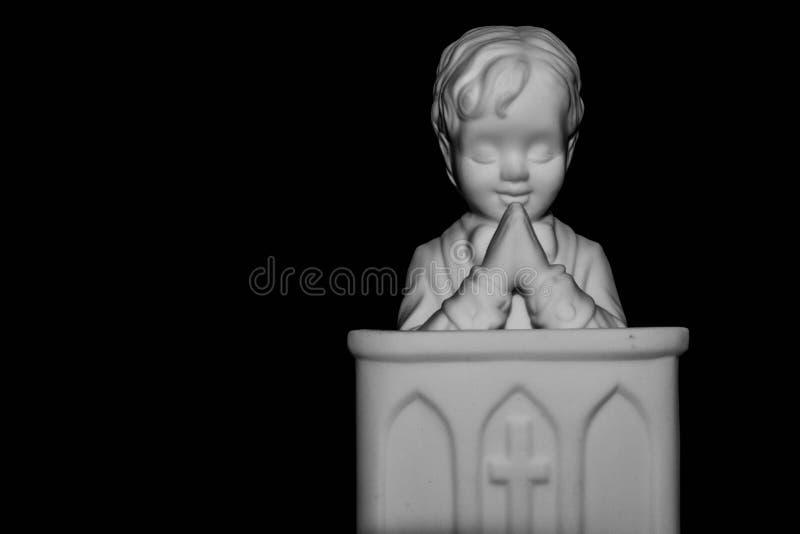 Weinig jongen die met zwarte achtergrond bidden stock afbeelding