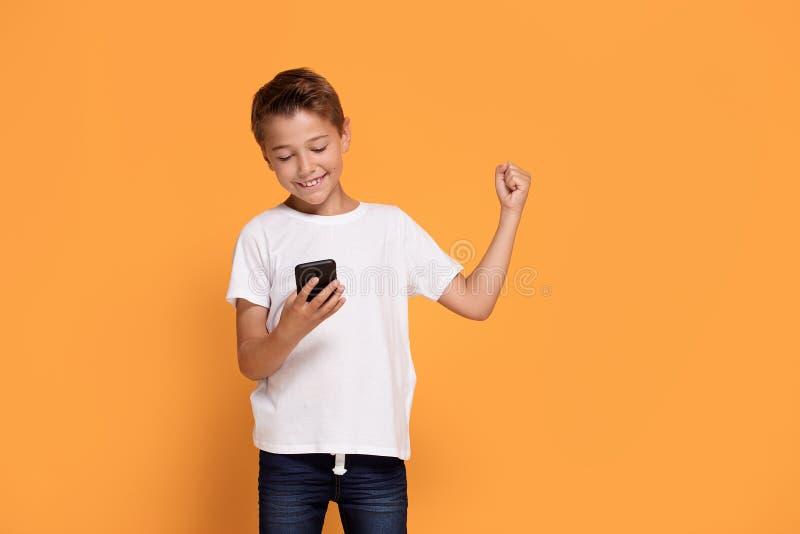 Weinig jongen die mobiele telefoon met behulp van stock fotografie
