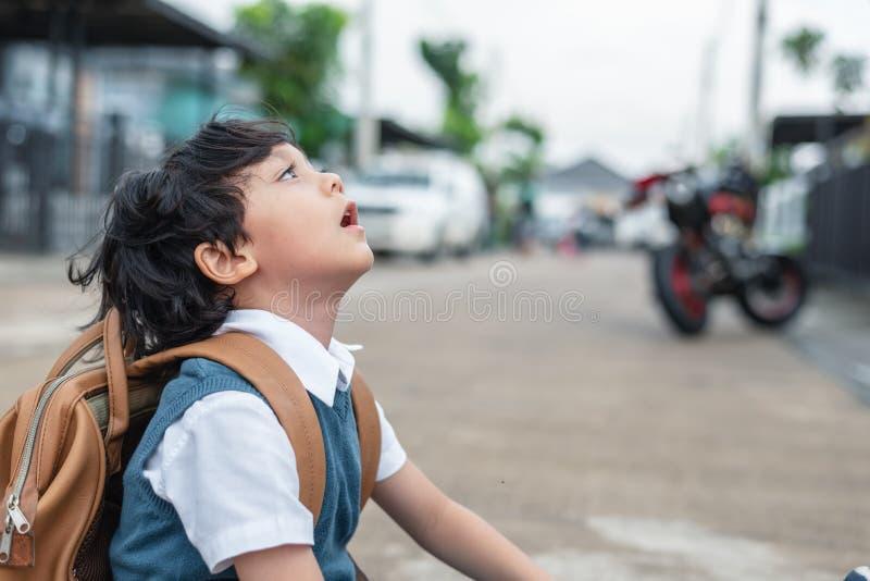 Weinig jongen die naar school in ochtend boring te gaan Havi van jonge geitjesstudenten stock fotografie