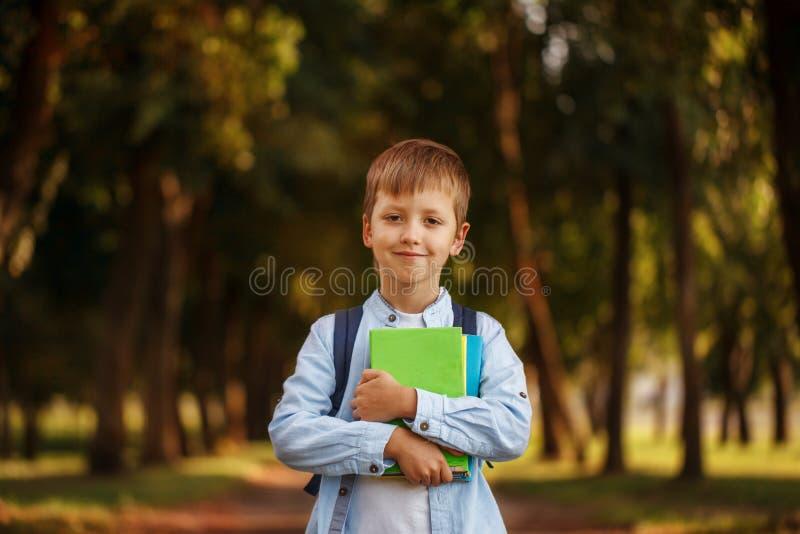 Weinig jongen die naar school terugkeert Kind met rugzak en boeken stock foto's