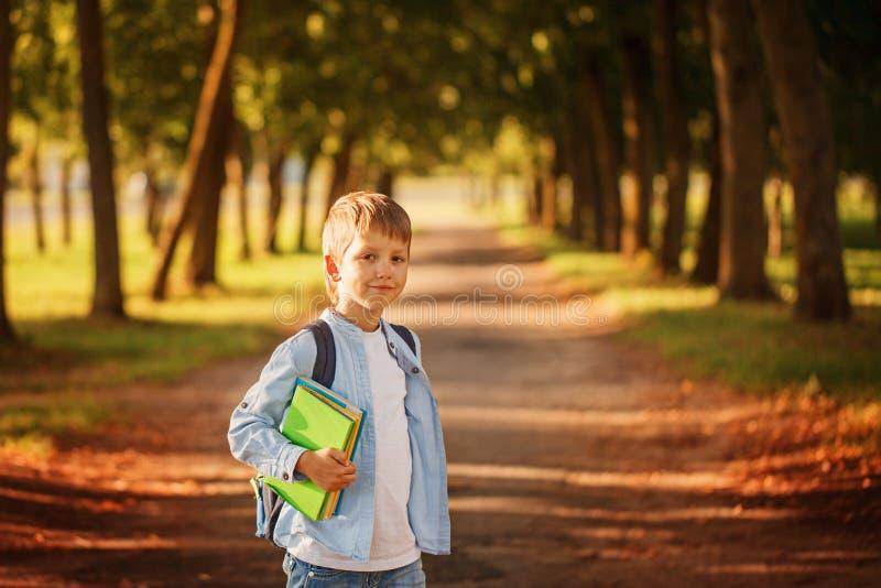 Weinig jongen die naar school terugkeert Kind met rugzak en boeken stock afbeelding