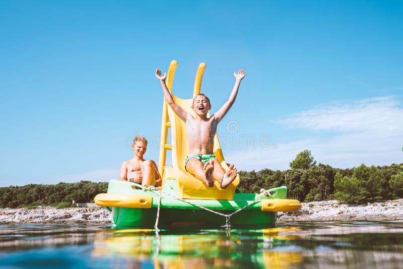 Weinig jongen die neer in zeewater van de drijvende Catamaran glijden van de Speelplaatsdia aangezien zij die van overzeese reis  stock foto's