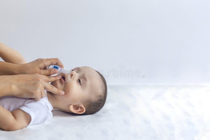 Weinig jongen die neusdalingen krijgen Pediater die zoute dalingen in de neus van de zuigeling zetten Moederhanden die de neus va royalty-vrije stock foto