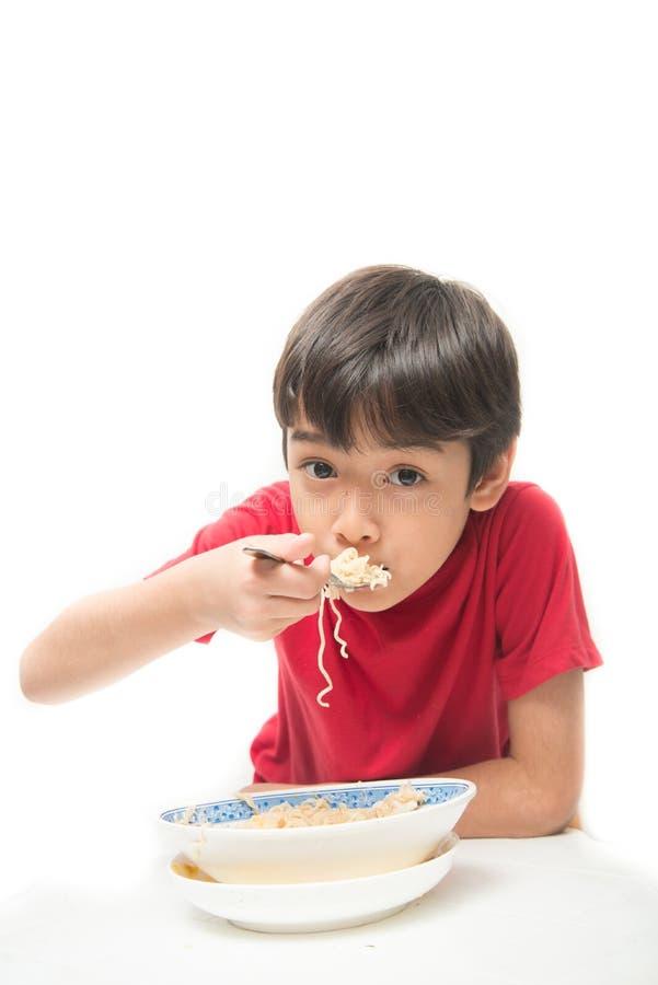 Weinig jongen die onmiddellijke noedel op witte achtergrond eten royalty-vrije stock foto