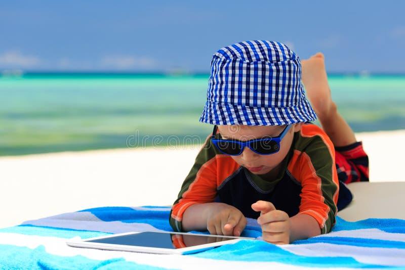 Weinig jongen die op aanrakingsstootkussen bij het strand spelen royalty-vrije stock afbeelding