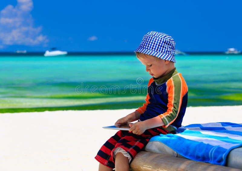 Weinig jongen die op aanrakingsstootkussen bij het strand spelen stock foto