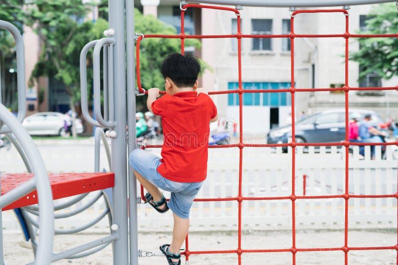 Weinig jongen die op aapbars bij speelplaats spelen stock foto