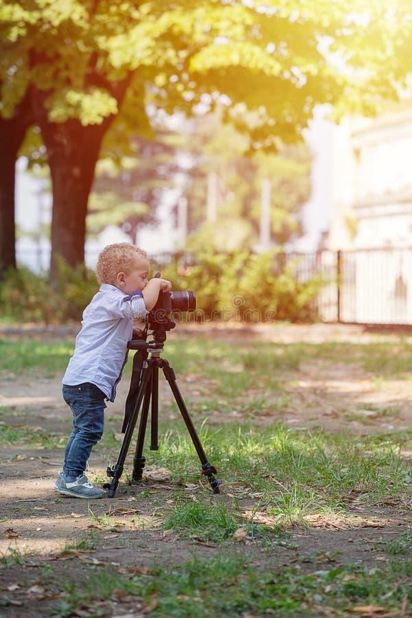 Weinig jongen die op de camera op driepoot in het park fotograferen royalty-vrije stock afbeelding